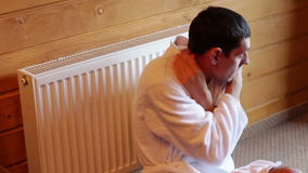 Man freezes near the radiator in the house stock video