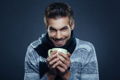 Man is freezing and holding cup of tea Royalty Free Stock Images