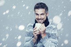 Man is freezing in the snow and holding cup of tea Royalty Free Stock Photos