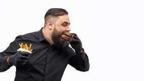 Man with french fries biting burger. Attractive bearded guy with portion of fresh french fries biting yummy burger and keeping eyes closed while standing against royalty free stock photography