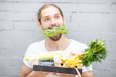 Man with fresh vegetables. Portrait of a handsome man biting green beans standing with box full of fresh vegetables on the brick wall background royalty free stock photography