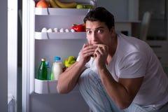 The man at the fridge eating at night. Man at the fridge eating at night Royalty Free Stock Photo