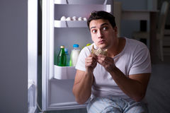 The man at the fridge eating at night stock photos