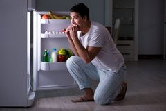 The man at the fridge eating at night Stock Image