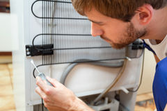 Man during fridge repair royalty free stock image