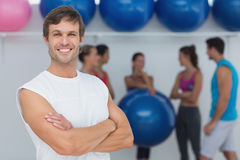 Man with friends in background at fitness studio Stock Photography