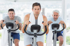 Man with friends on exercise bikes Royalty Free Stock Photo