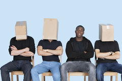Man with friends faces covered with cardboard boxes as they sit on chairs over blue background Stock Images