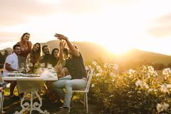 Group selfie at outdoor dinner party royalty free stock photography