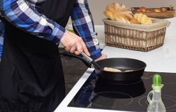 A man fries fatty cutlets in a pan, a lot of fat, junk food, close-up, homemade royalty free stock images