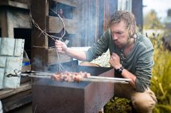 A man fries kebabs on Mongal in his garden plot. royalty free stock photography