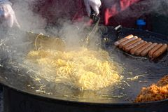 Man fries noodles on big frying pan, on street Stock Photography