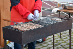 The man fries sausages on a street brazier. Food Royalty Free Stock Photo