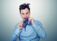 Man with frightened biting tie. Deep fear of businessman Royalty Free Stock Image