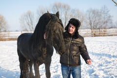Man with frisian horse Royalty Free Stock Images