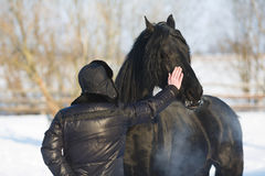 Man with frisian horse Stock Photography