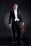 Man In Frock Coat. Man in a black frock coat and violin on a black studio background Stock Photo