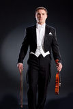 Man In Frock Coat With Violin. Man in a black frock coat with violin on a black studio background Stock Photo