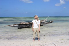 Man in front of the african boat on the seashore. Royalty Free Stock Images