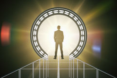 Man in front of amber teleport. Back view of businessman standing in front of abstract amber teleport with bright light. 3D Rendering Stock Photography