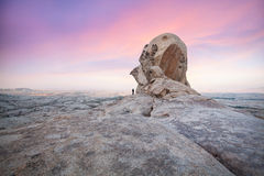 Man in front of big rock in stone desert Royalty Free Stock Photography