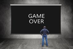 Man in front of black screen with words Game Over Royalty Free Stock Photography