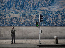 Man in front of blue tile wall. A solitary man stands in front of a blue tile church wall in Porto, Portugal Stock Photo