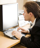 Man in front of computer screen. Shallow dof focus on keyboard Royalty Free Stock Images