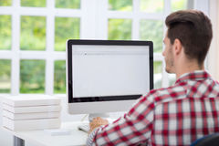 Man in front of computer. Young man looking at computer screen Stock Photo