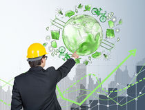 Man in front of eco energy icons, clean environment. Man in yellow helmet standing and pointing at the illustration of eco energy production on white wall behind Stock Image