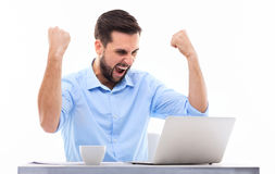 Man in front of laptop with arms raised Stock Images