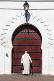A man in front of Mosque in Marrakech, Morocco. The name Marrakech originates from the Amazigh (Berber) words mur (n) akush, which means go and stop which was Stock Photo