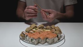 Man in front of a plate of sushi rolls opens sticks. Cooking stock video footage