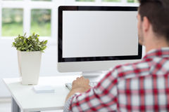 Man in front of screen. Young man looking at computer screen, working in bright office Stock Images