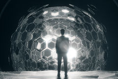 Man in front of silver sphere. Back view of businessman standing in front of cellular silver sphere on dark background. 3D Rendering. Technology concept Royalty Free Stock Image
