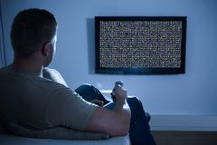 Man in front of television with no signal Royalty Free Stock Image