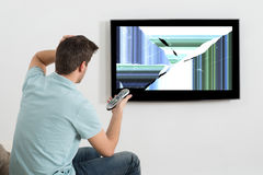 Man In Front Of Television Showing Distorted Screen. Frustrated Man Sitting On Sofa In Front Of Television Showing Distorted Screen stock images