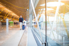 Man front walking at the airport using mobile phone Stock Photo