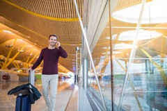 Man front walking at the airport using mobile phone Stock Images