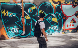 Man in front of wall with graffiti Royalty Free Stock Photo