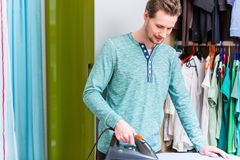 Man in front of wardrobe ironing the laundry. With iron stock photography