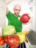 Man and fruits in refrigerator. A man reaching into a refrigerator to get fruits and vegetables Royalty Free Stock Photos