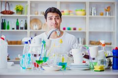The man frustrated at having to wash dishes. Man frustrated at having to wash dishes Stock Photos