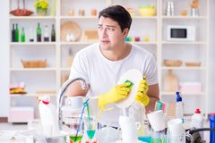 The man frustrated at having to wash dishes. Man frustrated at having to wash dishes Stock Photo