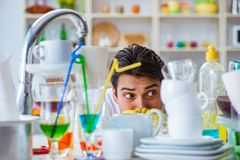 The man frustrated at having to wash dishes. Man frustrated at having to wash dishes Royalty Free Stock Photo
