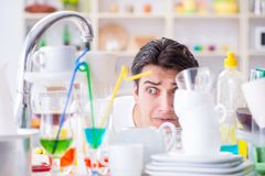 The man frustrated at having to wash dishes. Man frustrated at having to wash dishes Stock Photography