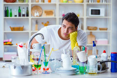The man frustrated at having to wash dishes. Man frustrated at having to wash dishes Royalty Free Stock Images