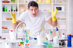 The man frustrated at having to wash dishes Stock Image