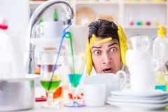 The man frustrated at having to wash dishes Stock Photos
