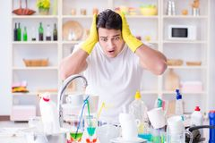 The man frustrated at having to wash dishes. Man frustrated at having to wash dishes Stock Images